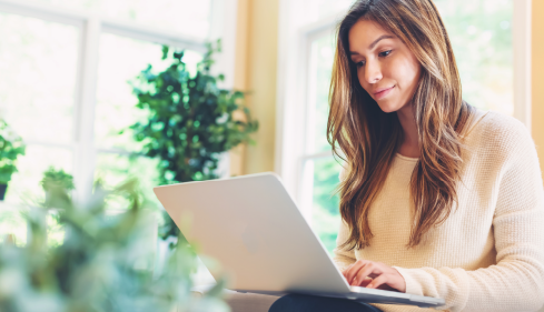 woman working on couch with laptop